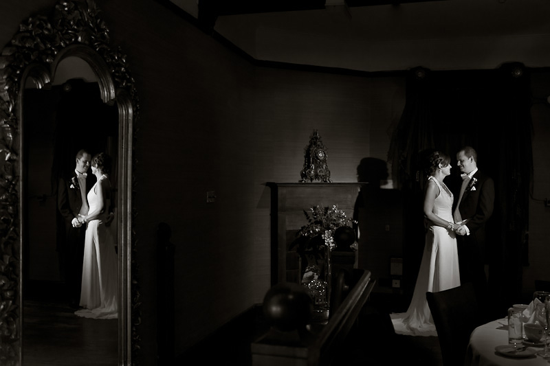 Bride and Groom holding hands with their reflection caught in the mirror