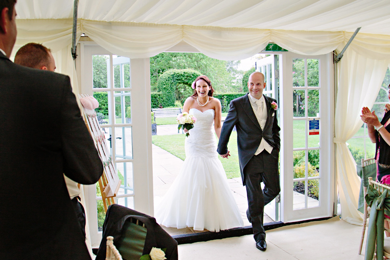 Guests clap the Bride and Groom as they enter the marquee