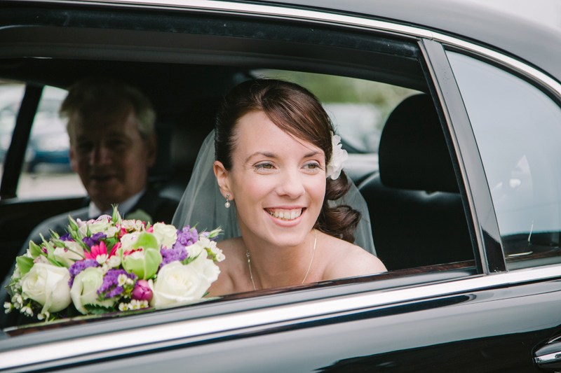Bride looking out of car window with dad next to her