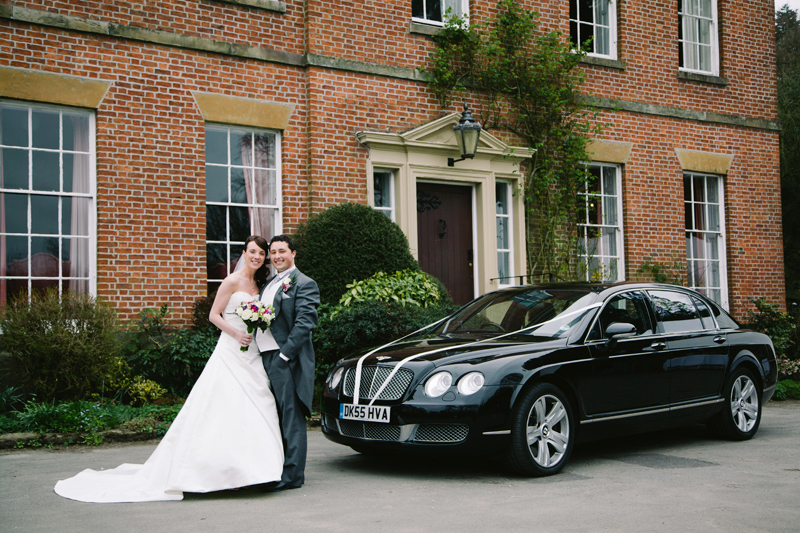 Bride and Groom with their wedding car on arrival at the venue