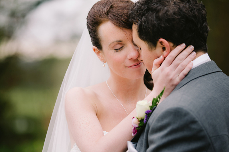 Bride caresses her husband's face