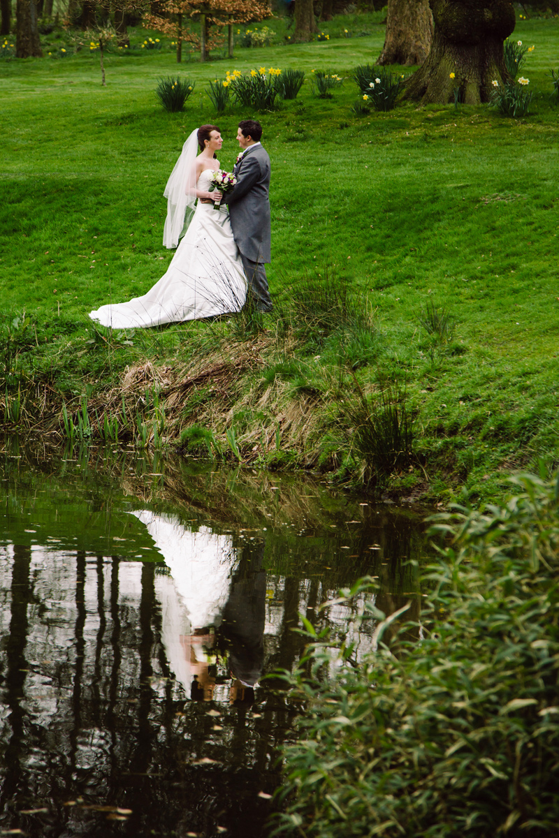 The Bride and Groom chat in a field of daffodils by a lake