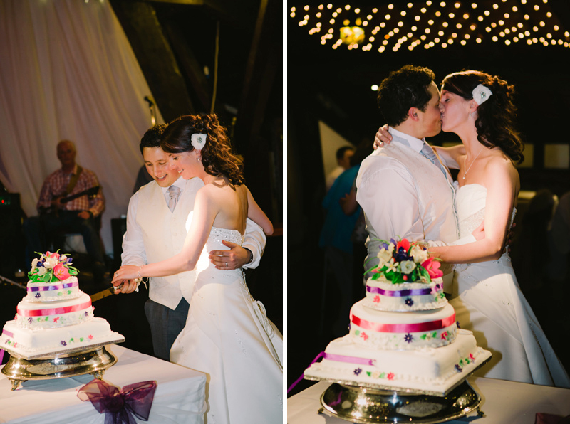 Bride and Groom cut their wedding cake in front of their guests