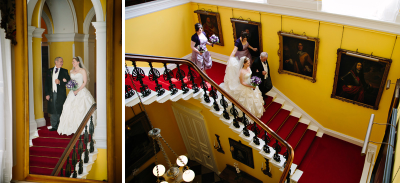 Bride and her dad walk down the staircase to the wedding ceremony