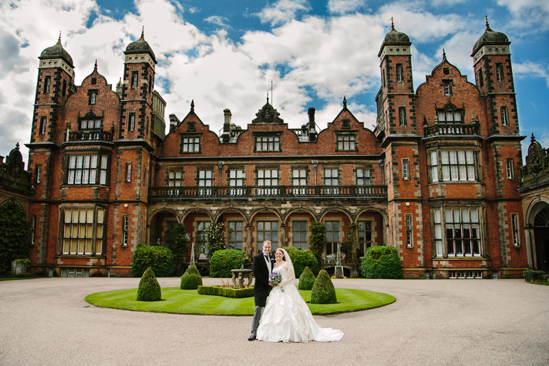 Bride and Groom standing in front of the grand main hall at Capethorne