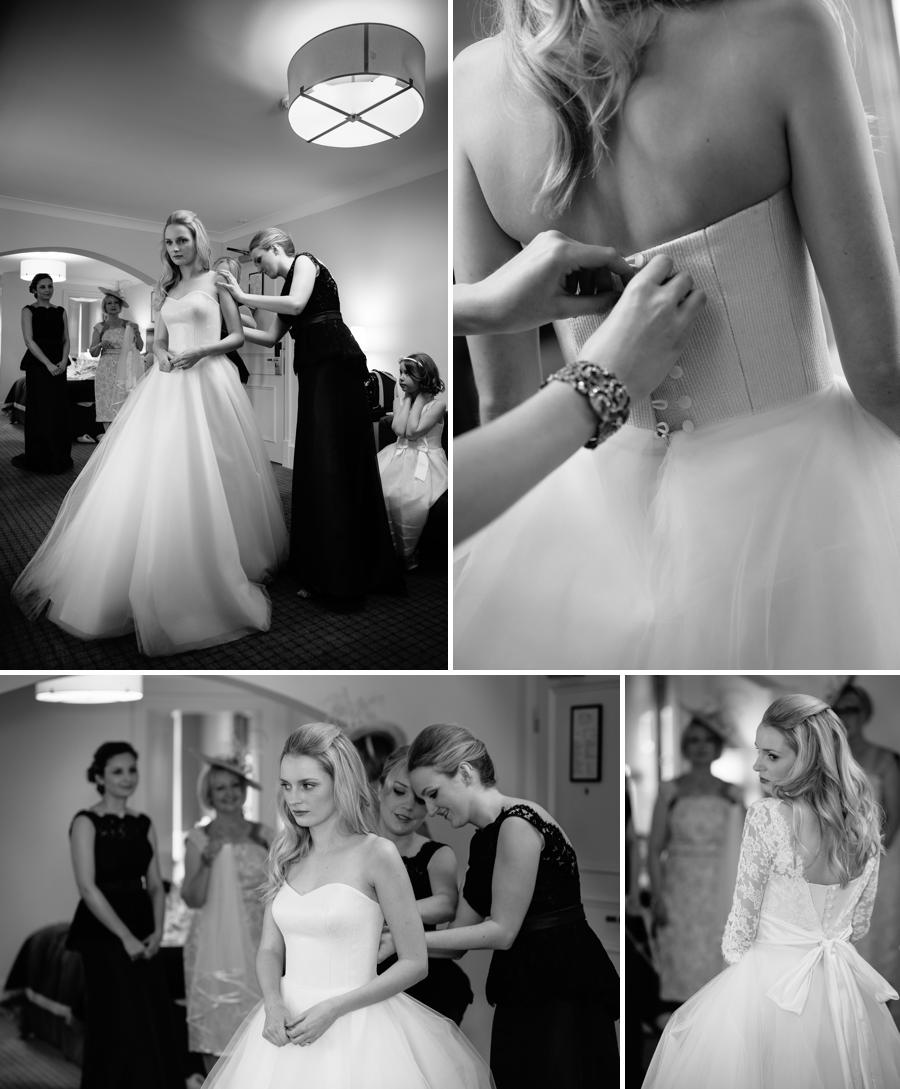 Bride getting into her wedding dress helped by the bridesmaids