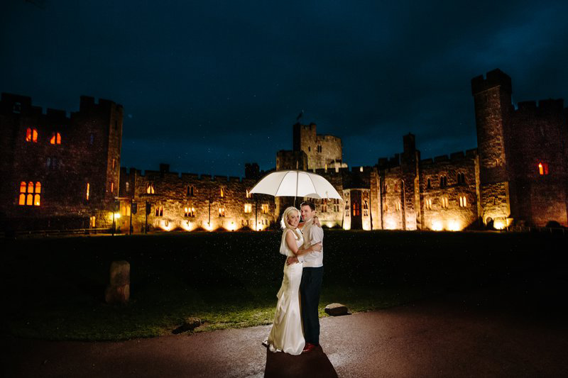 Bride and Groom under umbrella at night outside the castle