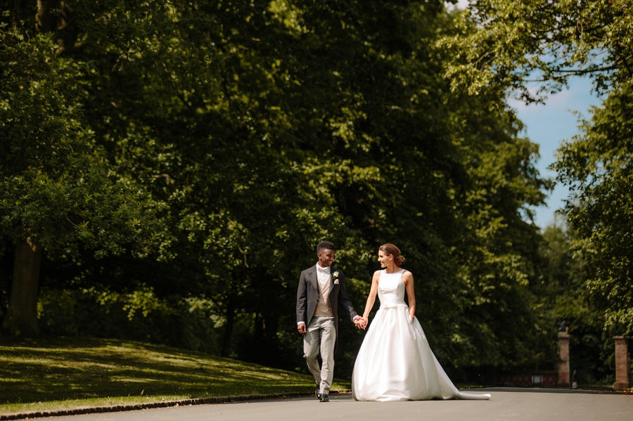 Bride and groom walking hand in hand down the driveway at Dorfold Hall