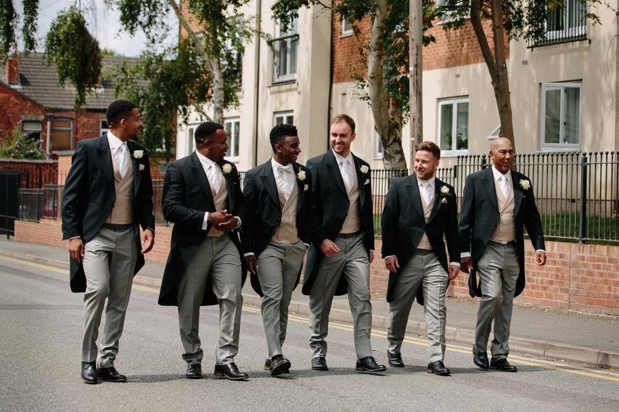 The groom and groomsmen walking to the church