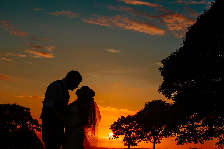 Bride and groom silhouette with a stunning sunset