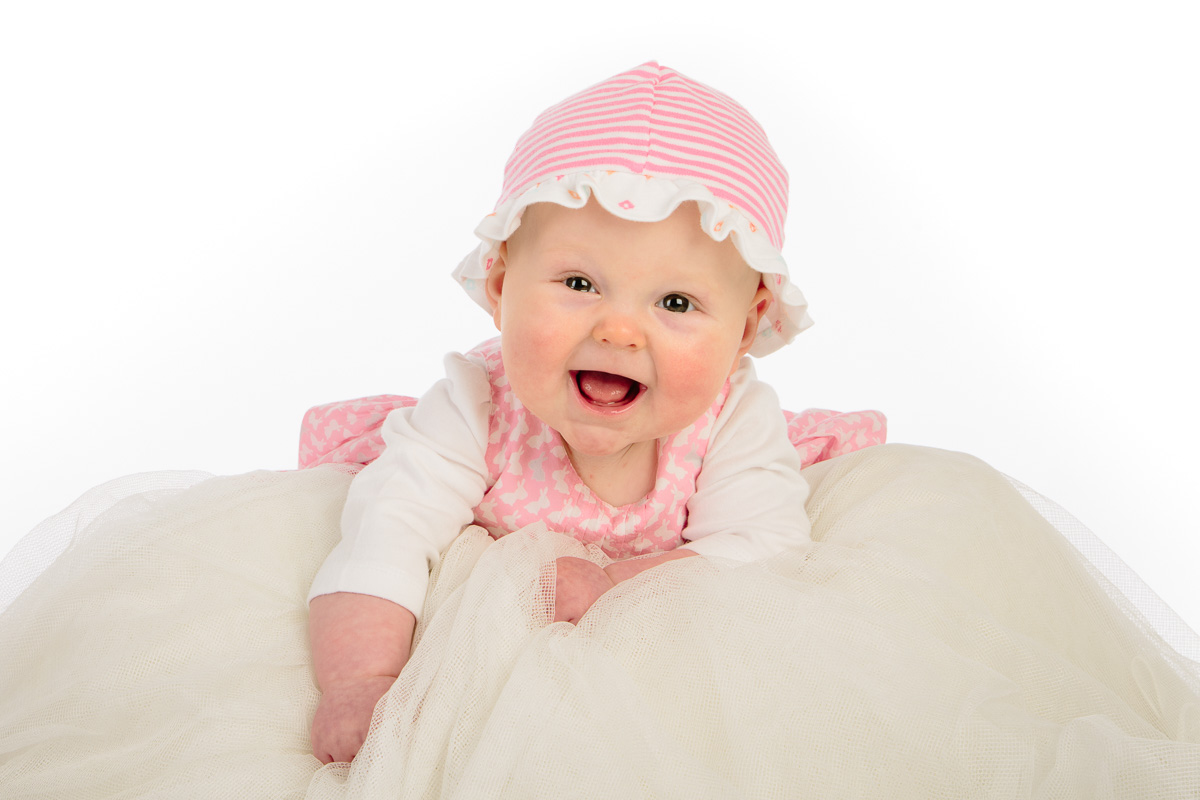 Baby in pink hat laughing