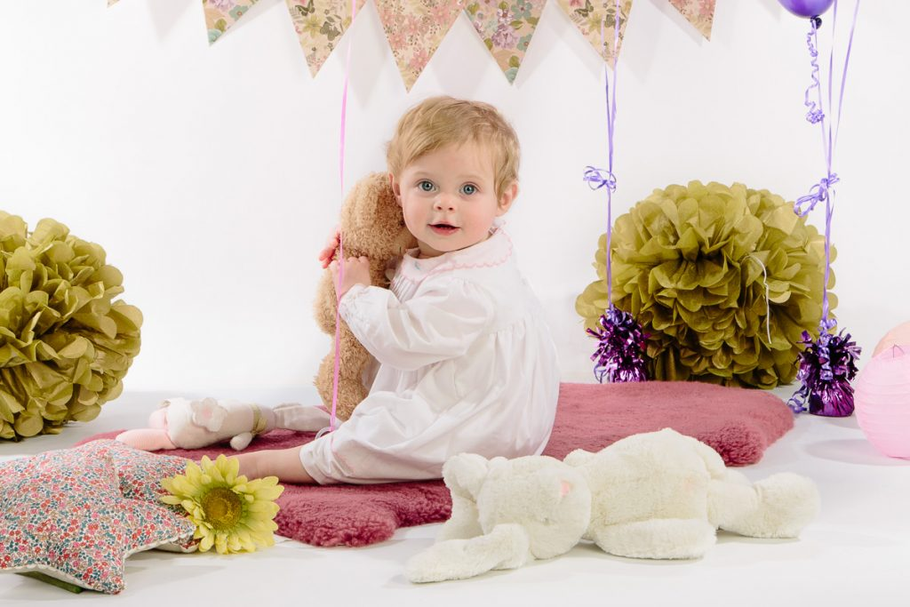 Little girl cuddling teddy with balloons in studio