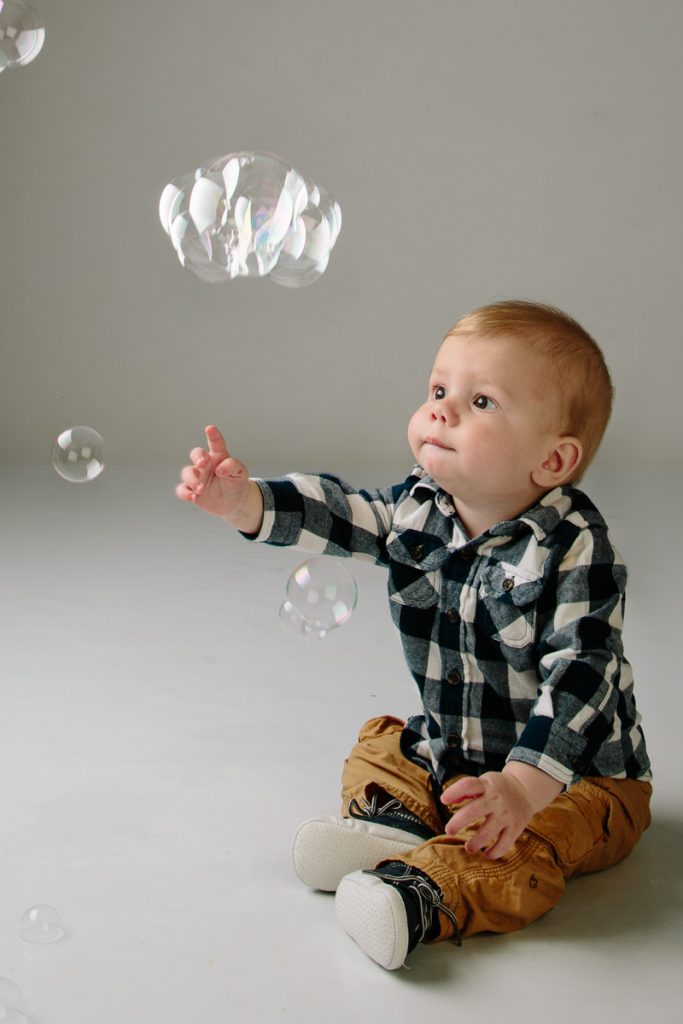 Boy playing with bubbles in studio