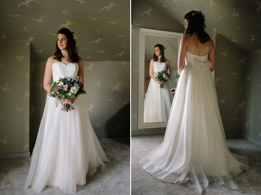Bride in her wedding dress looking at herself in the mirror
