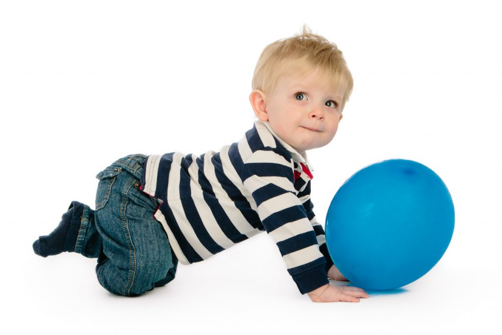 Little boy playing with balloon in studio