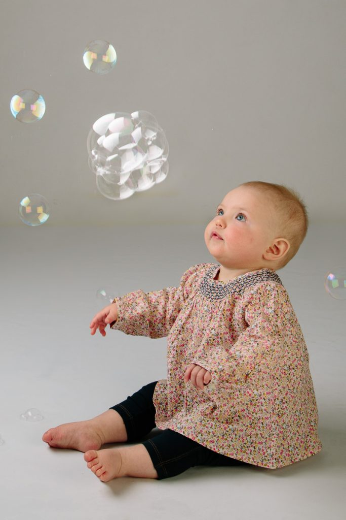 Baby trying to catch bubbles in studio