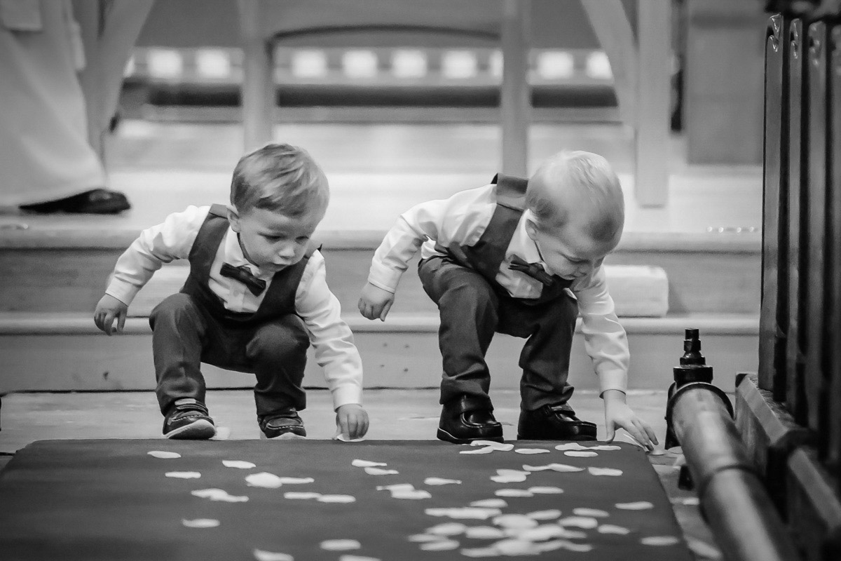 Page Boys playing with confetti in the Church