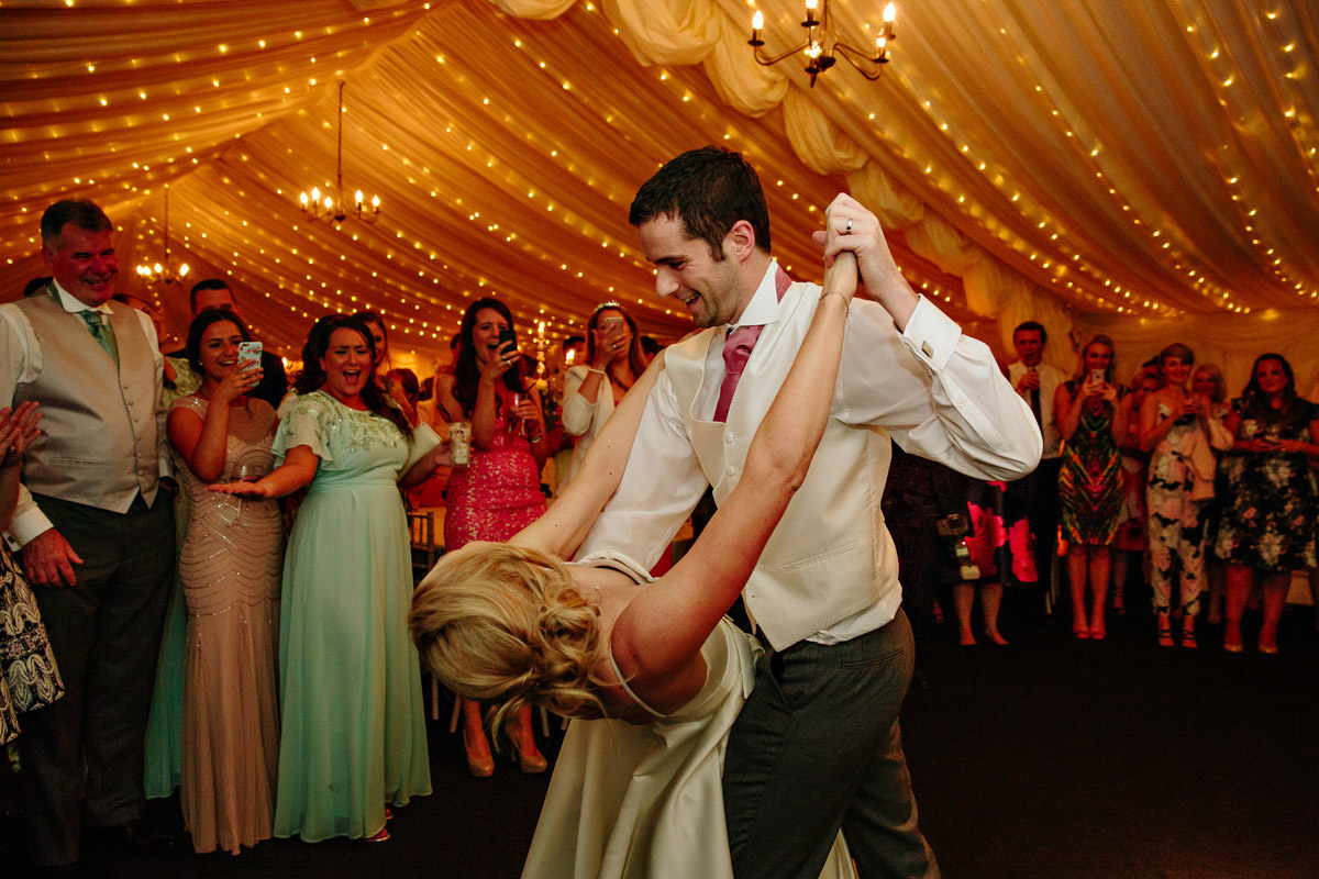 Groom dips his bride during the first dance while all of the guests look on laughing