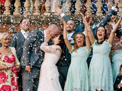 Bridesmaids  waving as confetti falls on bride and groom