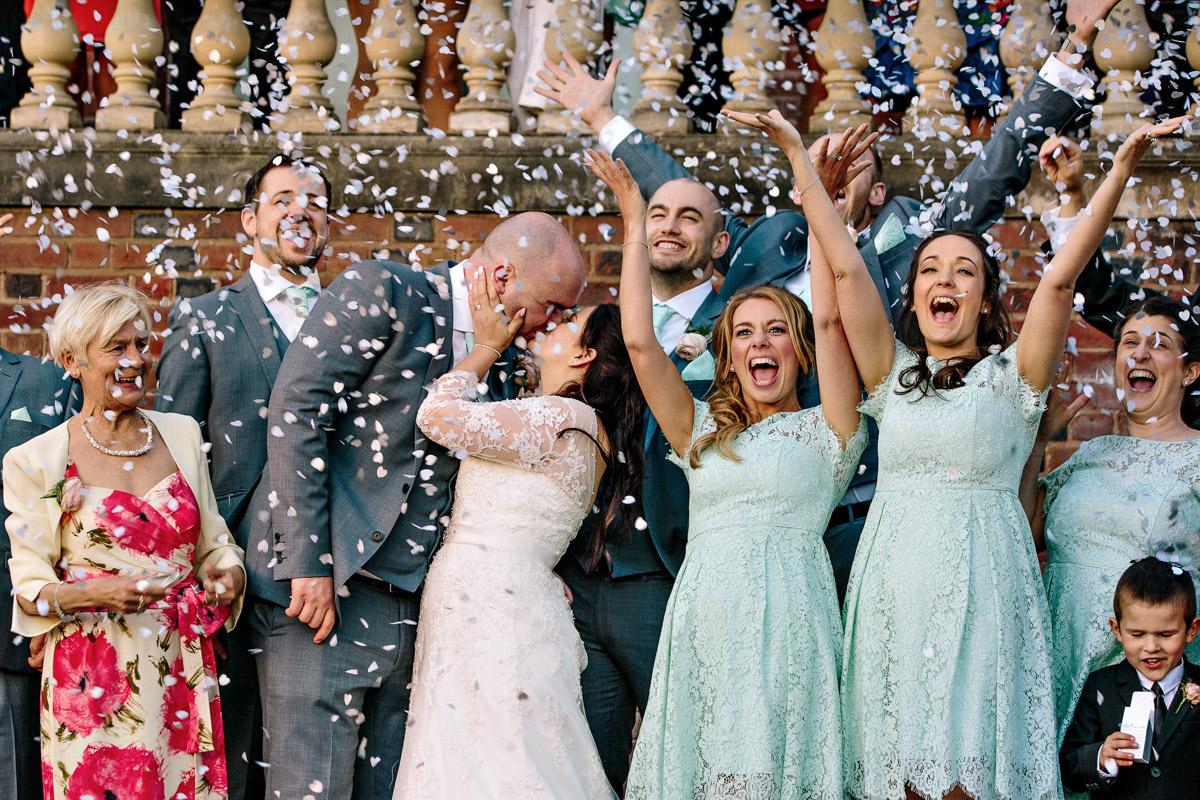 Bridesmaids  waving as confetti falls on bride and groom