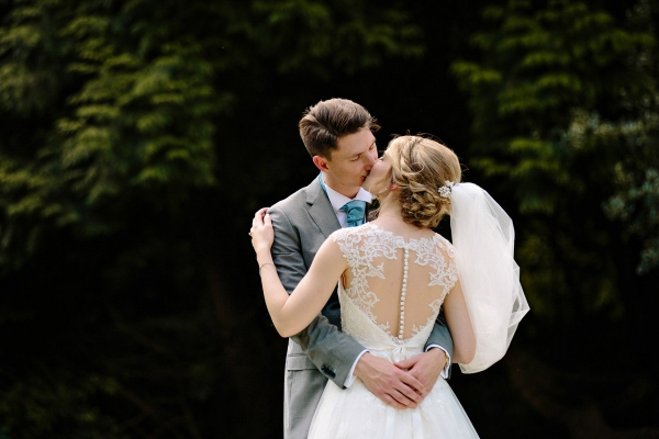 Bride and groom kissing showing the back of her wedding dress