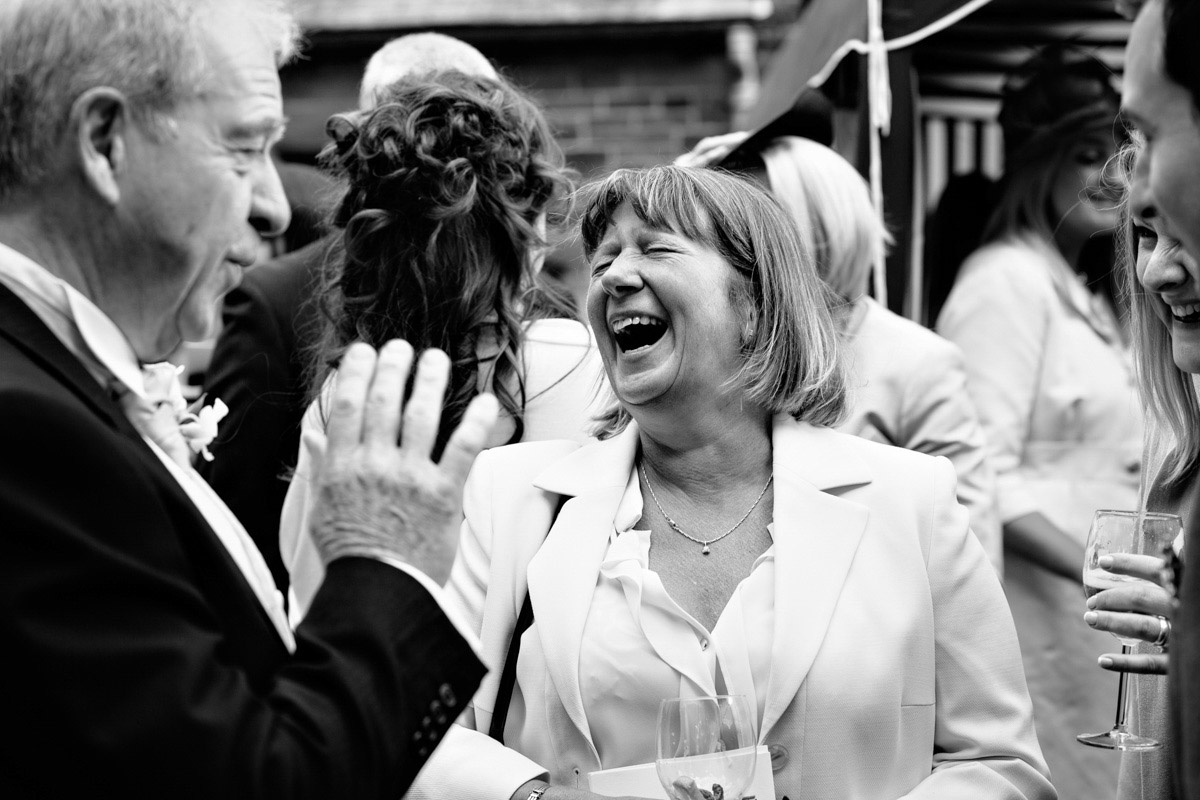 Wedding guests laughing during drinks reception at wedding