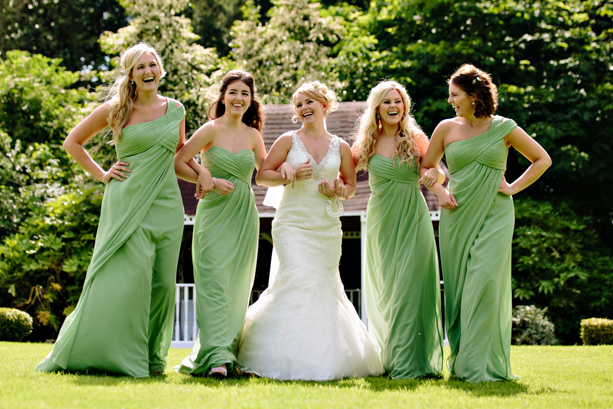 Bride and bridesmaids walking together in the sunshine at doubletree hilton in cheshire