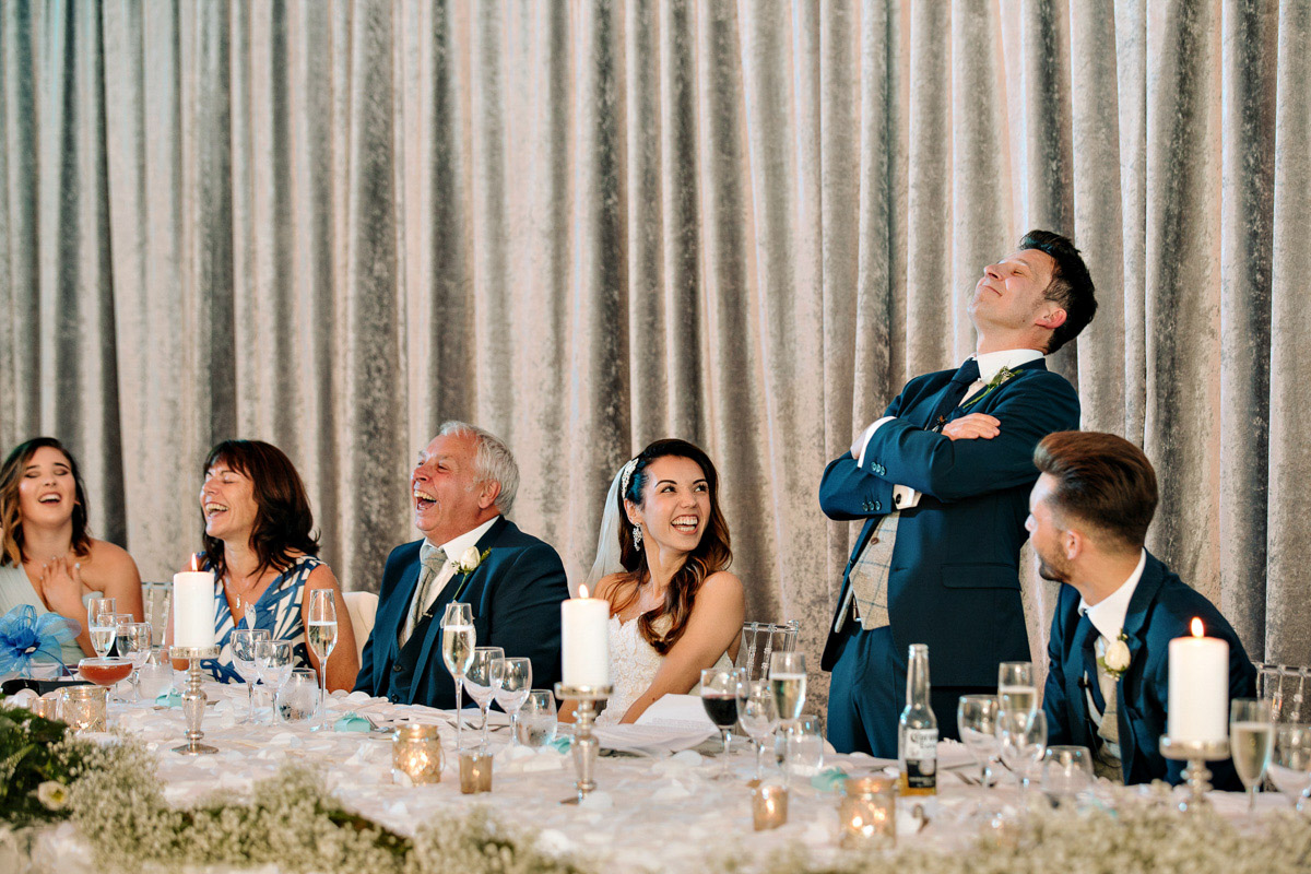 Wedding guests and bride and groom laughing at the wedding speeches