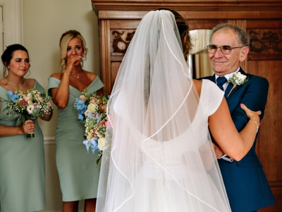 Father of the Bride seeing his daughter in her wedding dress for the first time while the bridesmaids look on crying