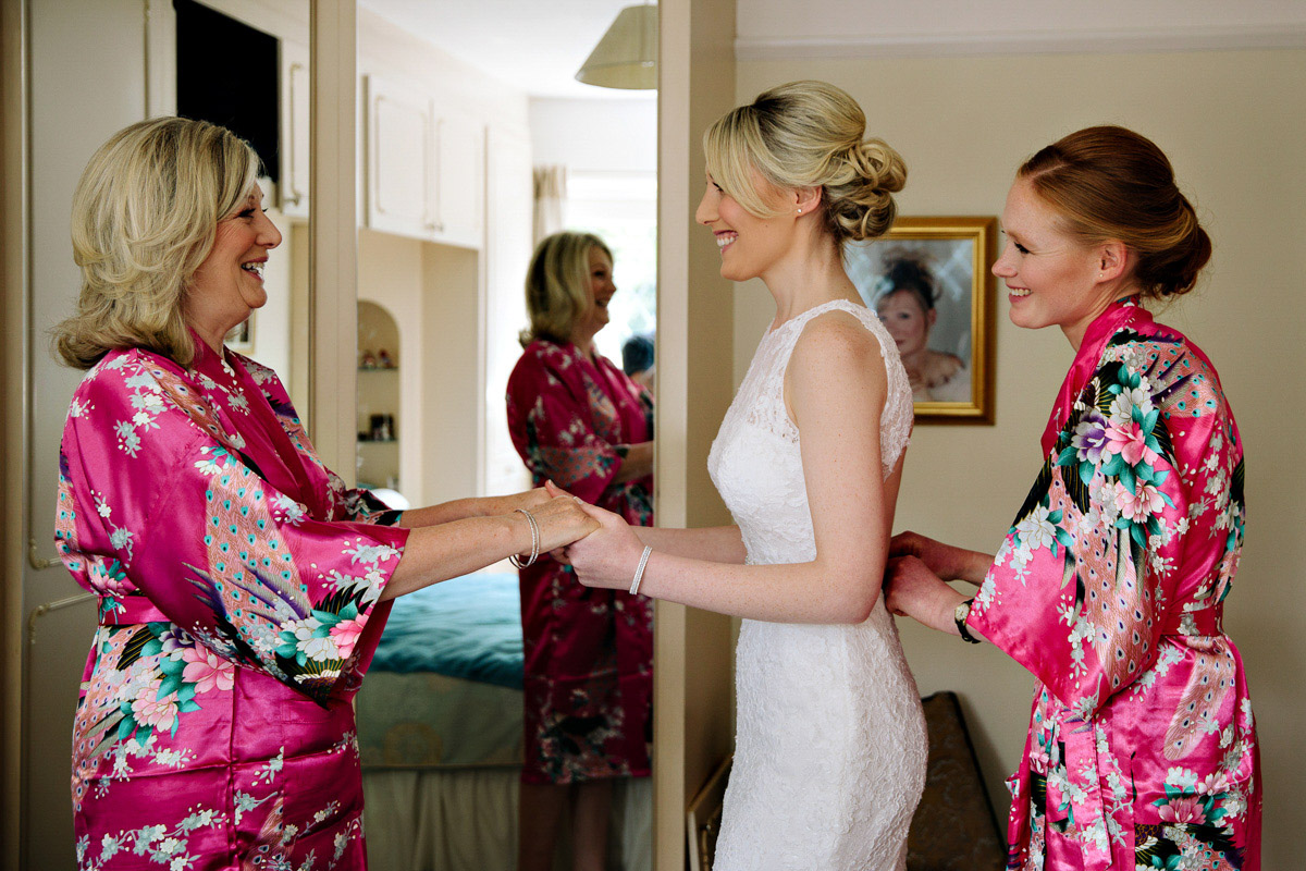 Mother of the Bride helping the Bride put on her wedding dress