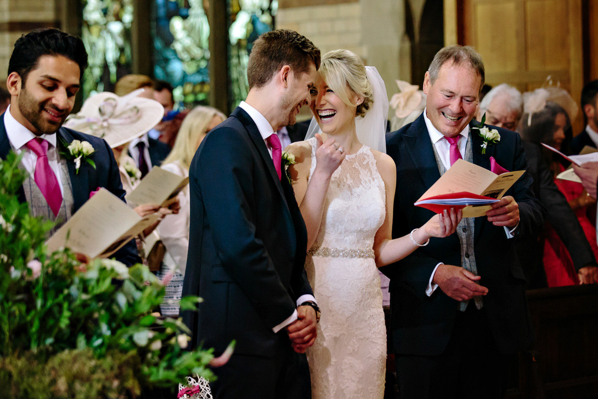 Bride laughing with groom at the altar in the church