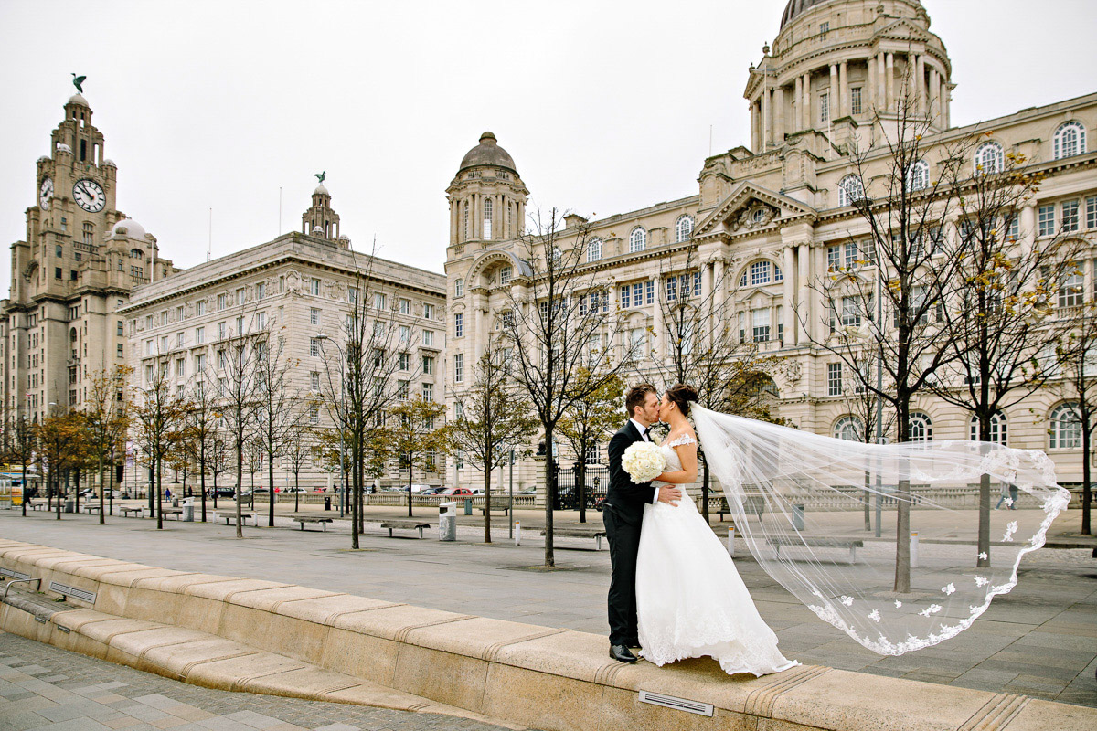 Bride and Groom with Veil blowing in the wind at Liverpool water front