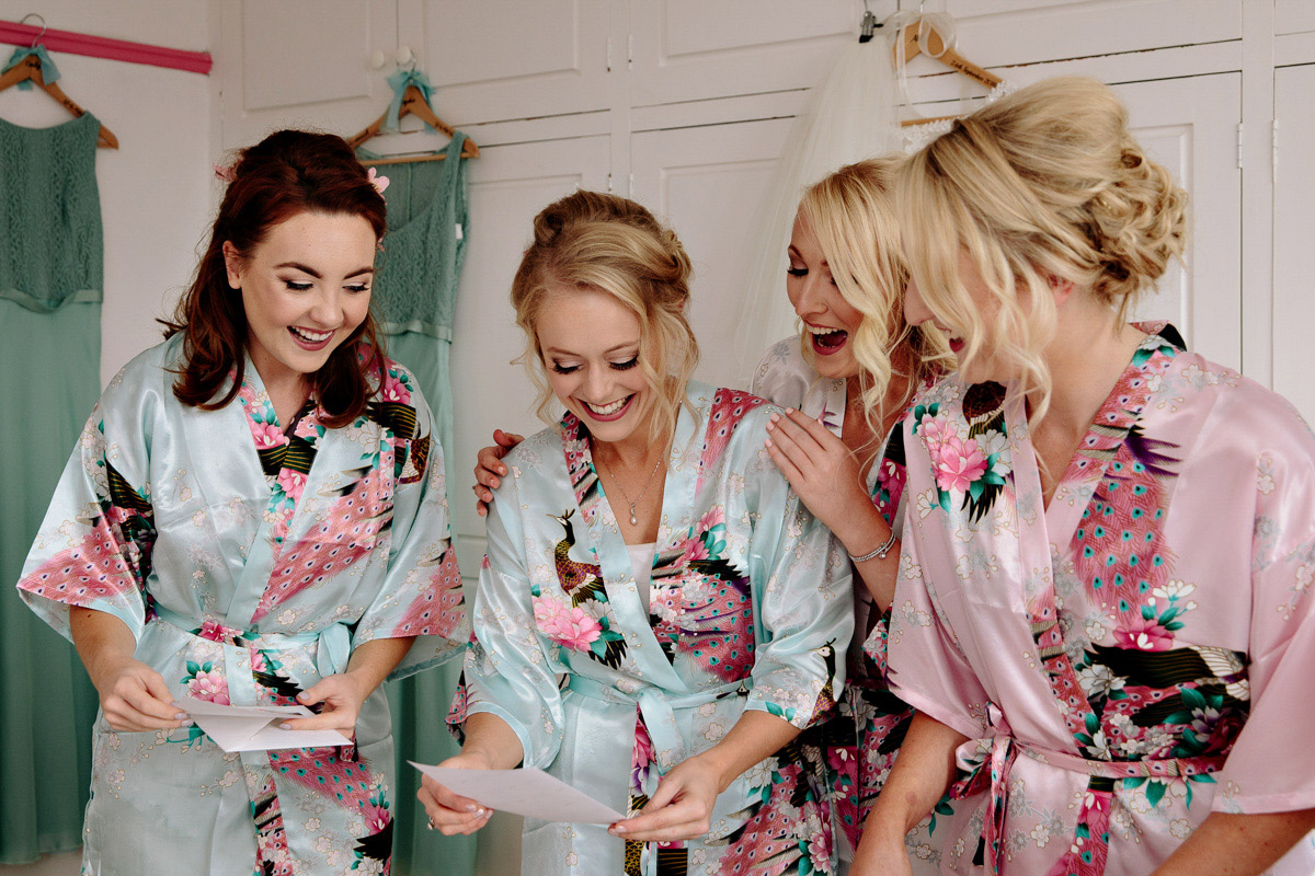 Bride and Bridesmaids opening presents during the bridal preparations
