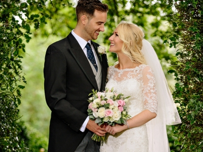 Bride and groom in archway at Rowton Hall in Cheshire