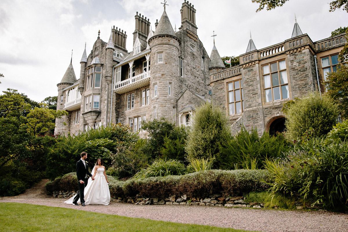 Bride and groom walking together at Chateau Rhianfa