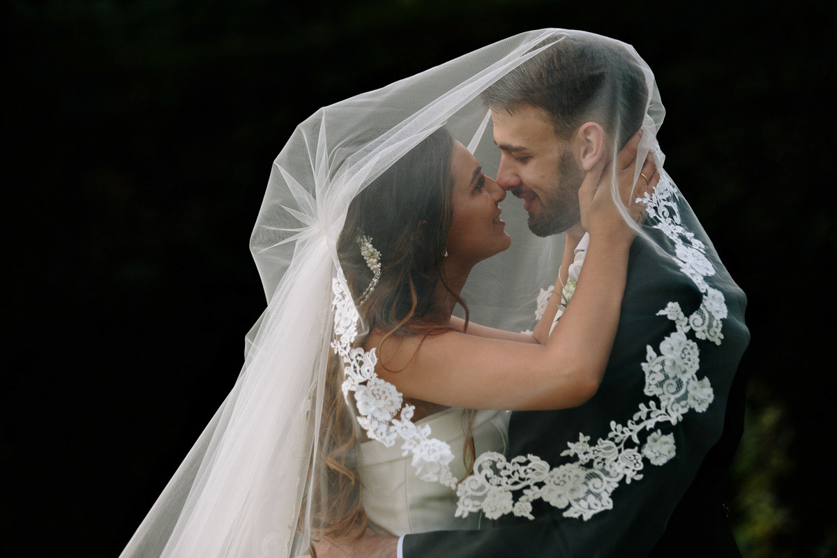 Bride and Groom under the veil together during the wedding