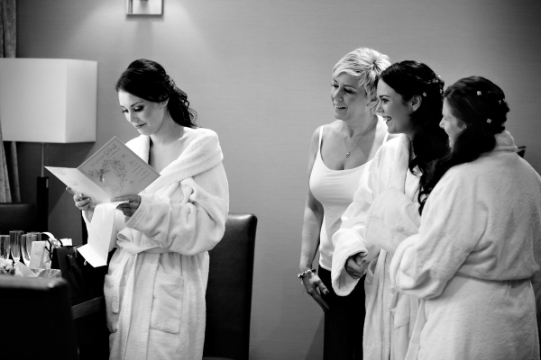 Bride opening her present with the bridesmaids and mother looking on