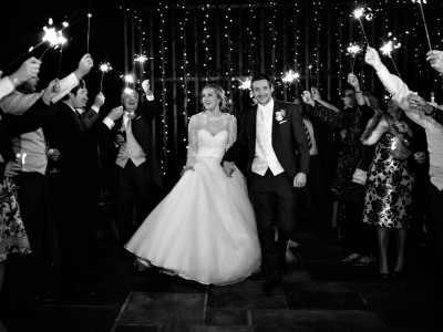 Bride and groom walking through a sparkler arch during the evening