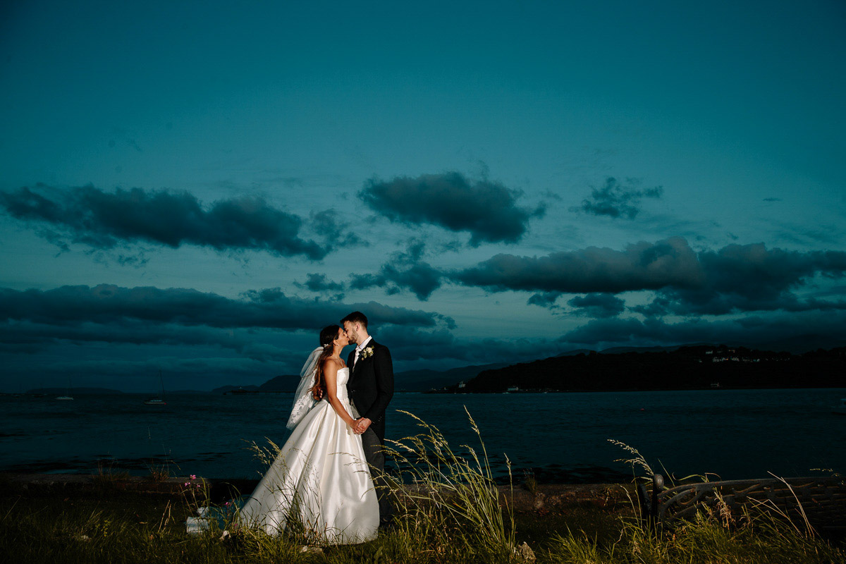 Stunning evening moment near the sea with the Bride and Groom sharing a kiss