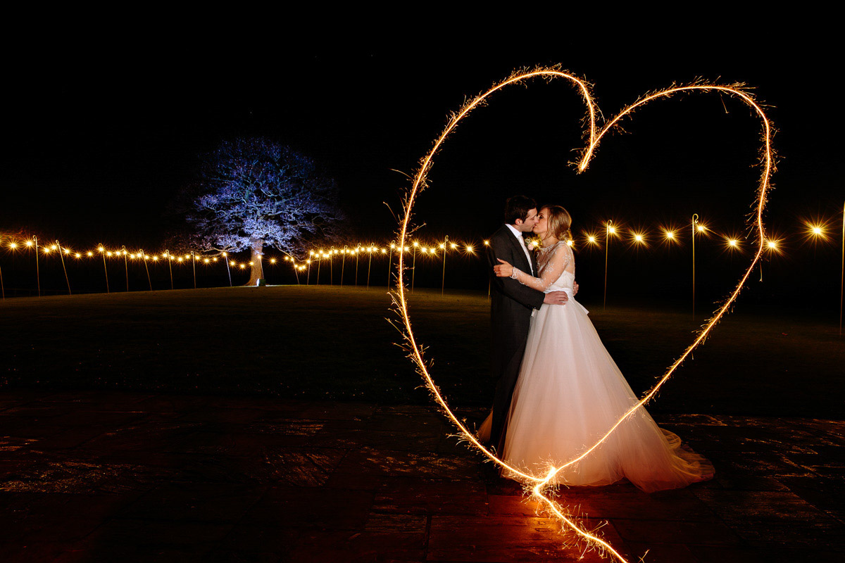 Sparkler heart image at Heaton House Farm with the Bride and Groom kissing