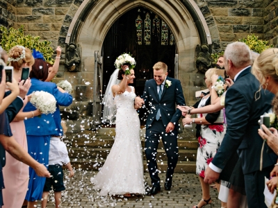 Bride and Groom leaving the church and getting showered in confetti from the wedding guests