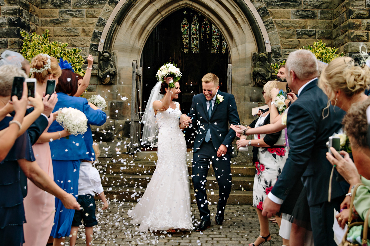Bride and Groom leaving church getting showered with confetti by the wedding guests