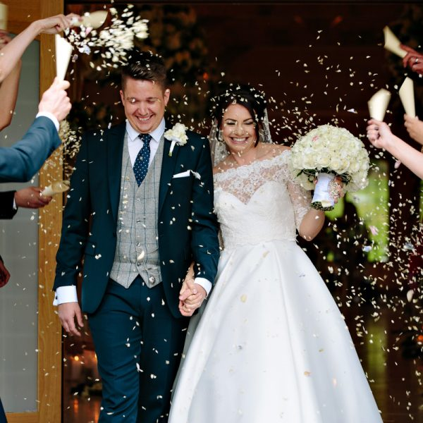 Stunning wedding with bride and groom being showered with confetti