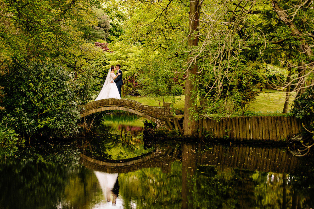 Bride and Groom on bridge with water reflection at Colshaw Hall in Cheshire
