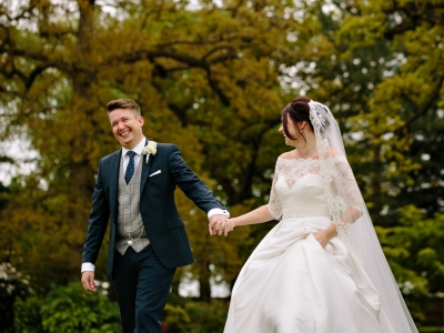 Groom laughing with the Bride as they go for a walk at Colshaw Hall in Cheshire