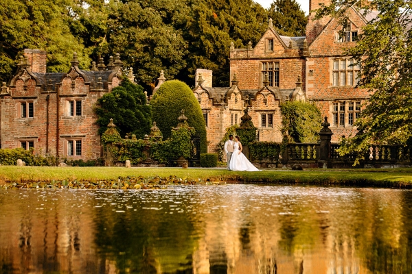 Bride and Groom with stunning reflection in the lake at Dorfold Hall in Cheshire