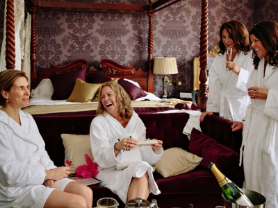 Bride and bridesmaids enjoying champagne during bridal preparations