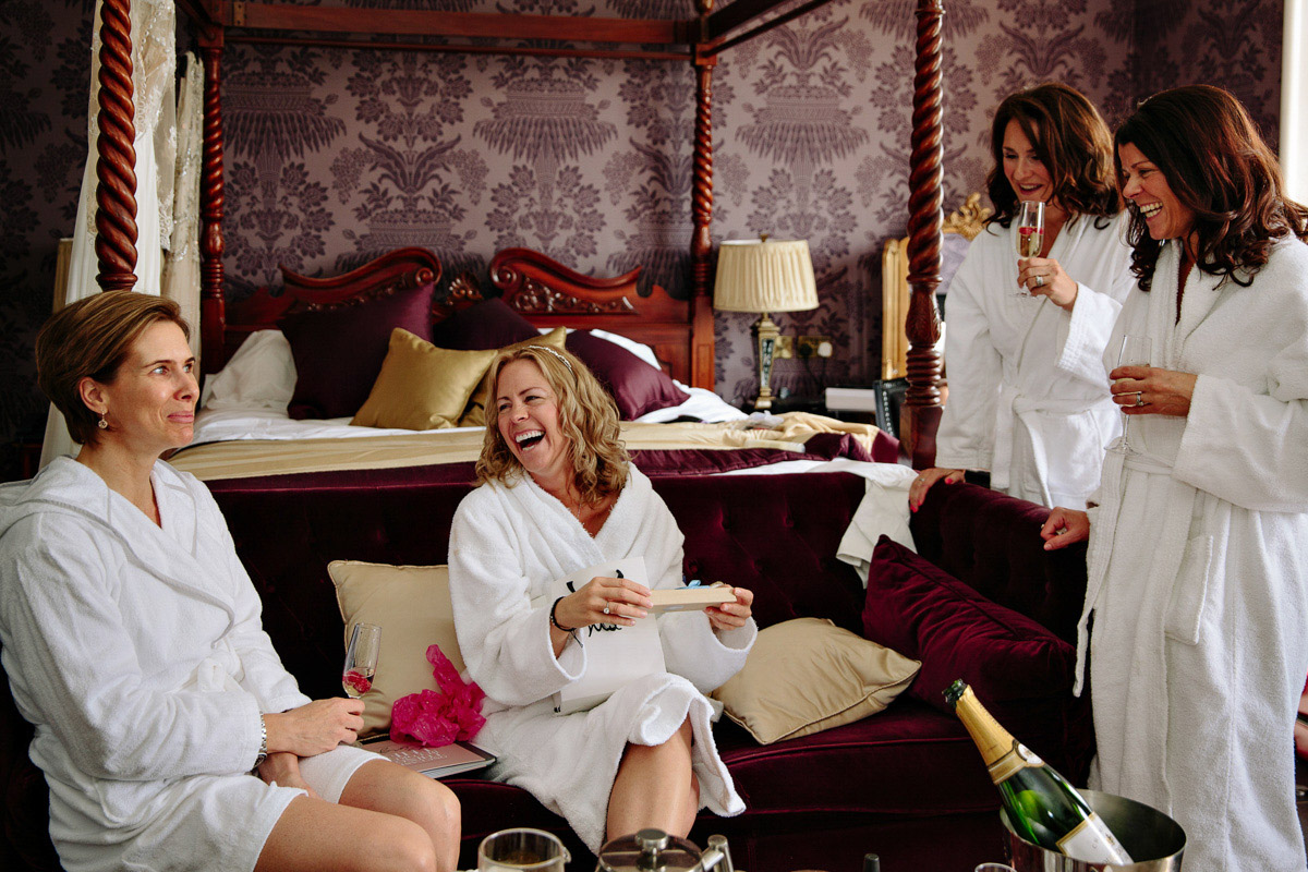 Bride and bridesmaids enjoying champagne during bridal preparations