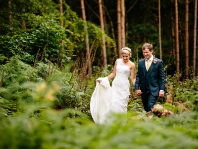 Bride and Groom walking through the forrest at Peckforton Castle in Cheshire