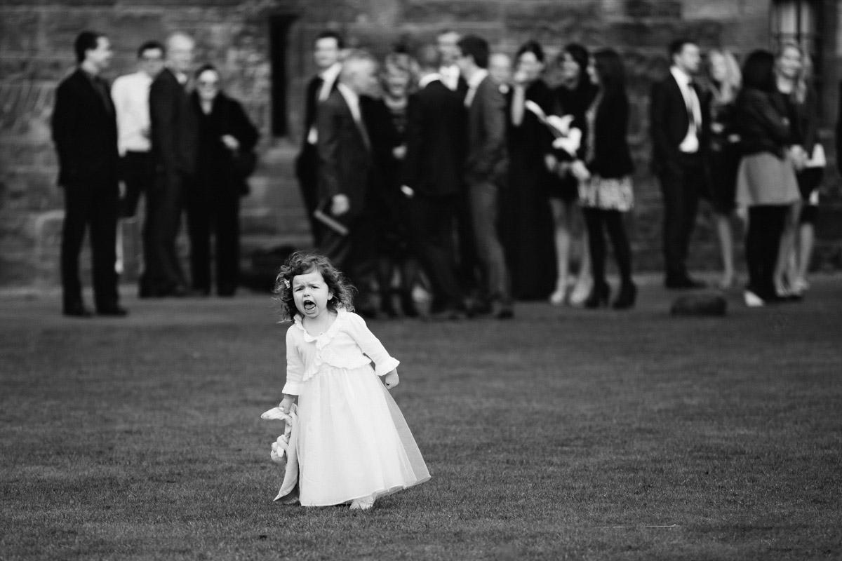 Flower girl running at Peckforton Castle in Cheshire